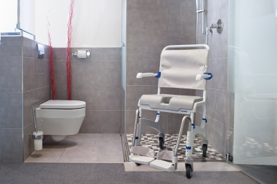 ... adjustable footrests, heel loops, height adjustable legs, with soft seat, hygiene opening, covered commode pan, 290lb capacity - Shown in bathroom
